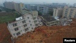 Tim pemadam kebakaran tengah berupaya melakukan pencarian korban di antara reruntuhan gedung yang terkena longsor di Shenzhen, provinsi Guangdong, 21 Desember 2015 - (REUTERS/Stringer)