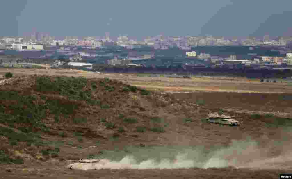 Israeli tanks can be seen as they drive on the Israeli side of the border with Gaza, August 8, 2014.