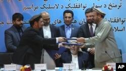 Perwakilan pemerintah Afghanistan, Attaurahman Saleem (kiri) dan Amin Karim, wakil dari kelompok Hizb-Islami (HIG), bertukar dokumen usai penandatanganan perjanjian damai di Kabul, Afghanistan, Kamis (22/9).
