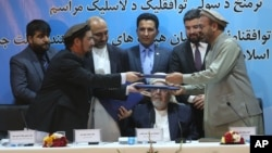 Amin Karim, representative of Gulbuddin Hekmatyar, right, and Attaurahman Saleem, head of delegation at peace talks, left, exchange documents after signing a peace deal in Kabul, Afghanistan, Thursday, Sept. 22, 2016.