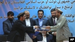 Amin Karim, representative of Gulbuddin Hekmatyar, right, and Attaurahman Saleem, head of delegation of peace talks, left, exchange documents after signing a peace deal in Kabul, Afghanistan, Thursday, Sept. 22, 2016.