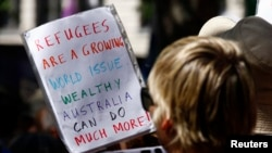 "Protesters hold placards at a ""Stand up for Refugees"" rally held in central Sydney, Oct. 11, 2014."