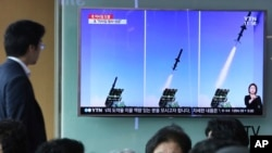 FILE - A man watches a TV news program showing photos published in North Korea's Rodong Sinmun newspaper of North Korea's new type of cruise missile launch, at Seoul Railway station in Seoul, South Korea, June 9, 2017.