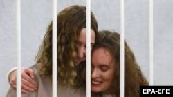 BELARUS -- Belsat journalists Katsyaryna Andreyeva (right) and Daryya Chultsova embrace each other in a cage before the start of a trial in Minsk, February 9, 2021