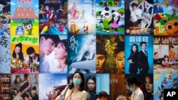 Visitors walk past a display of posters for Chinese movie and television productions at the China International Fair for Trade in Services in Beijing, Sept. 3, 2021.