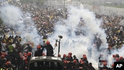 Malaysian riot police officers fire tear gas at activists from Coalition for Clean and Fair Elections (Bersih) during a rally in Kuala Lumpur, Malaysia, July 9, 2011