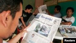 Warga Aceh membaca hasil pemilihan kepala daerah di Banda Aceh, 2006, dimana bekas pemberontak GAM menjadi gubernur.