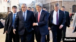 U.S. Secretary of State John Kerry holds onto Bulgarian Prime Minister Boyko Borisov as they walk around a patch of ice on the sidewalk after holding a joint news conference in Sofia, Jan. 15, 2015.
