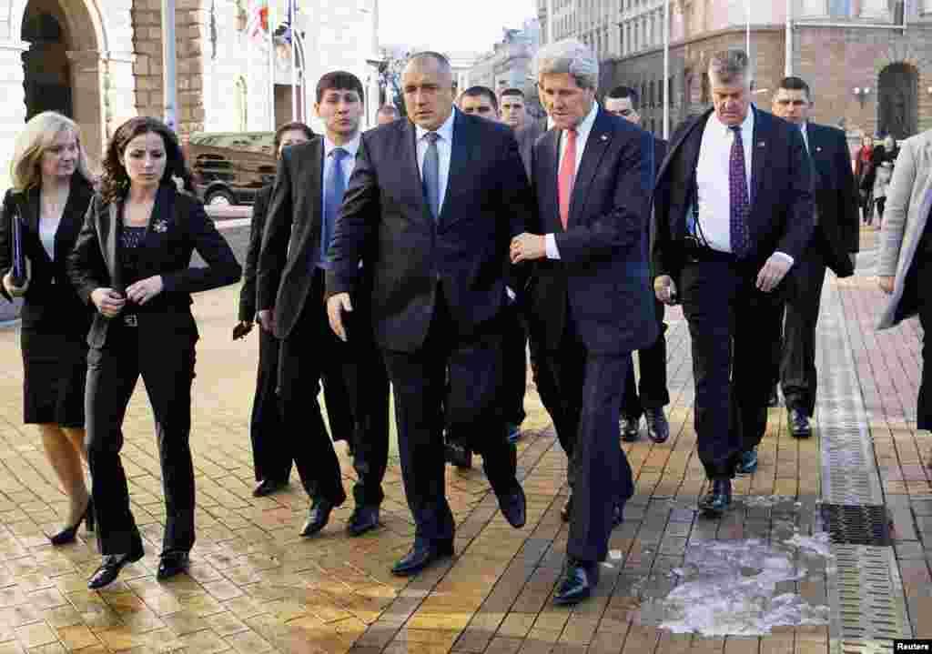 پس از پايان کنفرانس خبری صوفيه، وزير امورخارجه ايالات متحده آمريکا، جان کری، دست دربازوی نخست وزير بلغارستان، بويکو بوريسف، از روی زمين یخی عبور میکند.