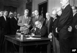 FILE - President Lyndon Johnson signs the Civil Rights Act in the East Room of the White House, July 2, 1964.