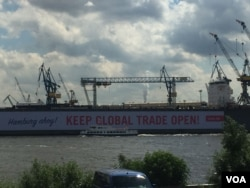 "Germany chose the port city of Hamburg as the site of this year's G-20 summit, opening Friday, as a sign that the country remains open in the face of what some perceive as growing isolationism and protectionist trade policies. The giant placard, which reads ""Hamburg Ahoy! Keep global trade open!"", was spearheaded by the New Social Market Economy Initiative, which describes itself as a cross-party NGO that supports a social market economy with fair competition and redistribution of wealth. (L. Ramirez/VOA)"