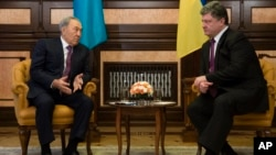 Kazakh President Nursultan Nazarbayev (L) speaks to Ukrainian President Petro Poroshenko during their meeting in Kyiv, Dec. 22, 2014.
