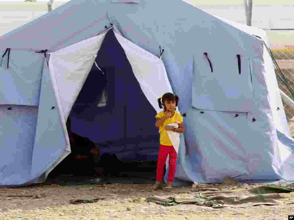 A refugee from Mosul stands outside her family's tent at Khazir refugee camp outside Irbil, Iraq, June 11, 2014.
