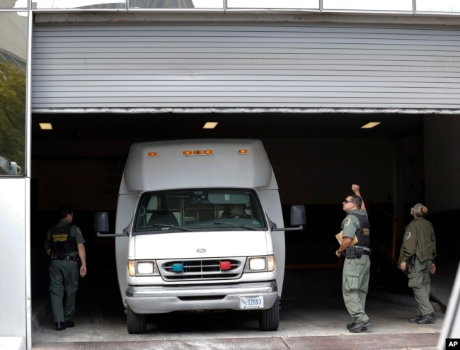 A van carrying asylum seekers from the border is escorted by security personnel as it arrives to immigration court, March 19, 2019, in San Diego, California.