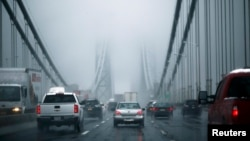 FILE - Cars make their way through the George Washington Bridge in New York City. New York and some other parts of the U.S. Northeast could be covered with more than 60 centimeters of snow in the coming days.