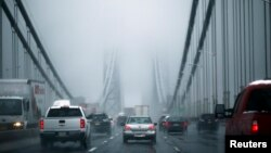 FILE - Cars make their way through the George Washington Bridge in New York City.