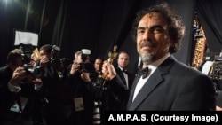 """FILE - Alejandro G. Iñárritu backstage with the Oscar® for Original screenplay, for work on """"Birdman or (The Unexpected Virtue of Ignorance)"""" during the live ABC Telecast of The 87th Oscars® at the Dolby® Theatre in Hollywood, California, Feb. 22, 2015."""