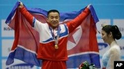 지난 20일 남자 역기 56kg급 경기에서 북한의 엄윤철 선수가 세계 신기록과 아시아 신기록을 세우며 금메달을 목에 걸었다.