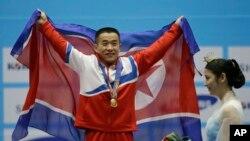 지난 해 아시아경기대회에서 세계 신기록과 아시아 신기록을 세우며 금메달을 목에 건 엄윤철 선수가 인공기를 들고 환호하고 있다.