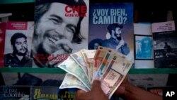 쿠바 수도 아바나의 한 노점상이 전통 페소화 지폐와 (왼쪽 3장)와 환전이 가능한 페소화 지폐를 함께 들고 있다.