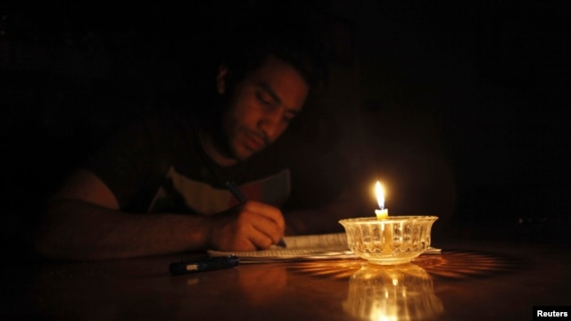 Mostafa Khaled, 20, studies by candlelight for his early morning exams during a power cut in Toukh, about 25 km northeast of Cairo, May 26, 2013.