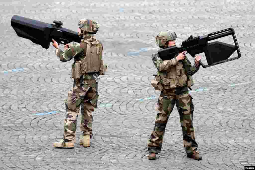 Dua Tentara Prancis memegang senjata anti-drone selama parade militer memperingati Hari Bastille di Champs-Elysees Avenue, Paris.