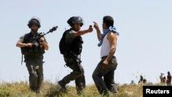 Seorang polisi Israel mengacungkan semprotan merica ke arah seorang warga Palestina untuk membubarkan bentrokan antara pemukim Yahudi dan warga Palestina di desa Urif dekat Nablus, Tepi Barat (30/4).