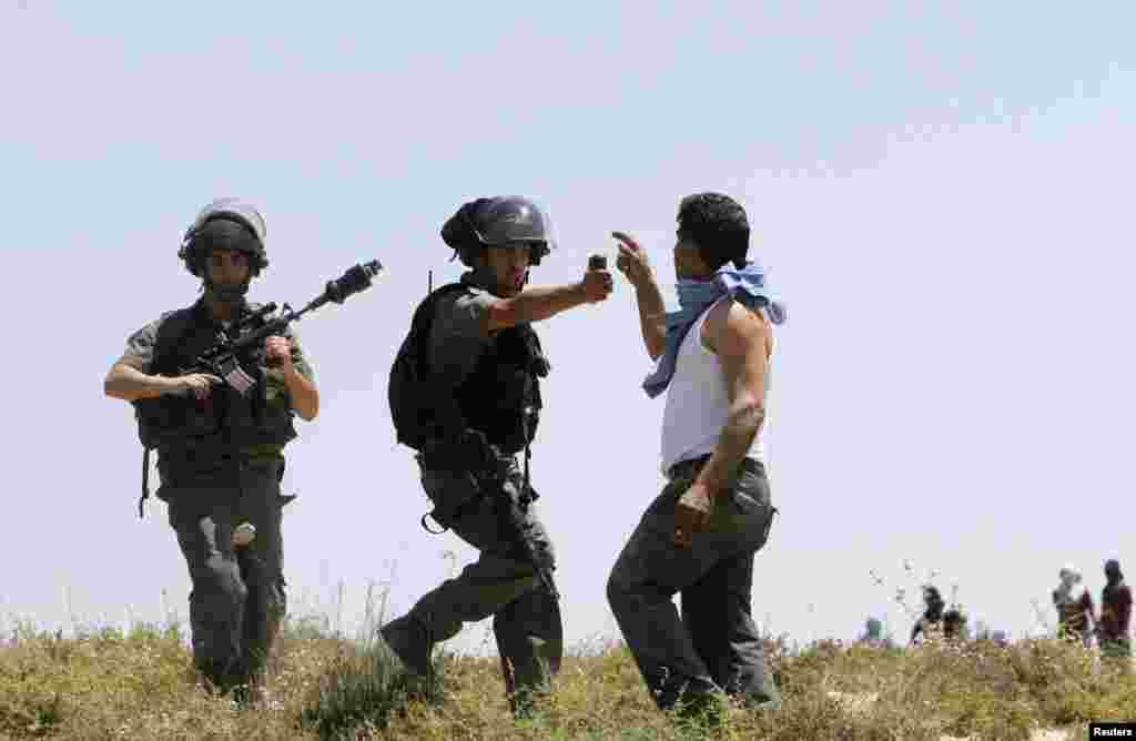 Lính biên phòng Israel cầm bình xịt hơi cay nhắm vào một người Palestine trong khi xô xát diễn ra giữa những người định cư Do Thái và người Palestine ở làng Urif thuộc Bờ Tây, gần Nablus.