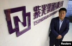 资料照:紫光集团董事长赵伟国站在该集团北京办公室的标识前。(2015年11月15日)
