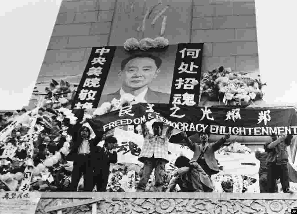 """中国学生在北京天安门广场上的人民英雄纪念碑前展示胡耀邦像和""""民主之光耀邦""""等标语(1989年4月19日) 。1989年4月15日,抑郁中的胡耀邦突然心梗病逝,引发民众不满和自发悼念,直接触发后来的八九民运和""""六四事件""""。而这也导致胡耀邦多年来成为中共党内的禁忌,直到团派出身的前总书记胡锦涛任内才逐渐解禁,并于2015年11月20日为他举办百岁诞辰座谈会。"""