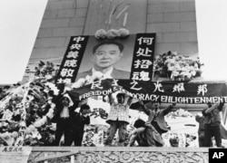 """中国学生在北京天安门广场上的人民英雄纪念碑前展示胡耀邦像和""""民主之光耀邦""""等标语(1989年4月19日)"""