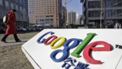 A woman walks past the logo of Google in front of its headquarters in Beijing January 12, 2011