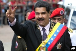Venezuela's President Nicolas Maduro flashes a victory sign to supporters as he arrives to the Supreme Court to deliver his annual state of the nation report in Caracas, Venezuela, Sunday, Jan. 15, 2017.
