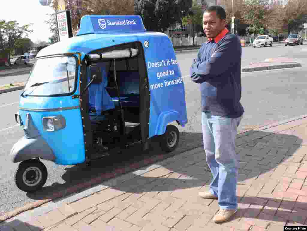 """People call our tuk tuks 'toy cars,'"" says Johannesburg driver Alan Bangi as he waits for a fare at a Sandton intersection. (Photo by Darren Taylor)"
