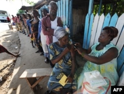 FILE - A health worker administers a yellow fever vaccine to a woman on August 27, 2008 on a roadside in Koumassi, a poor quartier of Abidjan after a case was discovered of yellow fever.