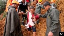 Rescatistas ayudan a una mujer y su hijo para evacuarla a un área más segura luego de derrumbes en el municipio de Itogón, provincia de Benguet, en el norte de Las Filipinas. Los deslizamientos de tierra, que sepultaron a decenas de mineros y han aislado la población son consecuencia del tifón Mangkhut. Septiembre 16 de 2014.