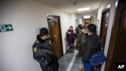 Một cảnh sát Azerbaijan (trái) đứng canh trong khi các ký giả tụ tập tại trụ sở đài RFE trong thủ đô Baku, 26/12/14