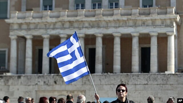 A woman raises a Greek flag during an anti-austerity rally in front of the parliament in Athens February 19, 2012.
