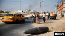 8月一日巴勒斯坦民眾圍觀一枚沒有爆炸的以色列炸彈落在加莎的主路上。