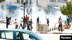 Des protestataires dispersés par des gaz lacrymogènes à Kairouan, en Tunisie.