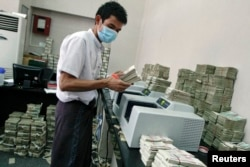 FILE - An employee counts Myanmar kyat banknotes in a bank in Yangon, April 5, 2012.