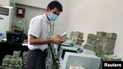 FILE - An employee counts Myanmar kyat banknotes in a bank in Yangon, April 5, 2012. The United States said on Wednesday it was ready to relax some sanctions on Myanmar.