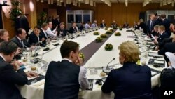 British Prime Minister David Cameron, center left, talks during the round table meeting of European Union heads of state and government at an EU summit in Brussels, Feb. 19, 2016.