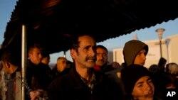 在希腊与马其顿的边界上的一个难民营里,叙利亚难民排队领取食物。(2016年2月25日)