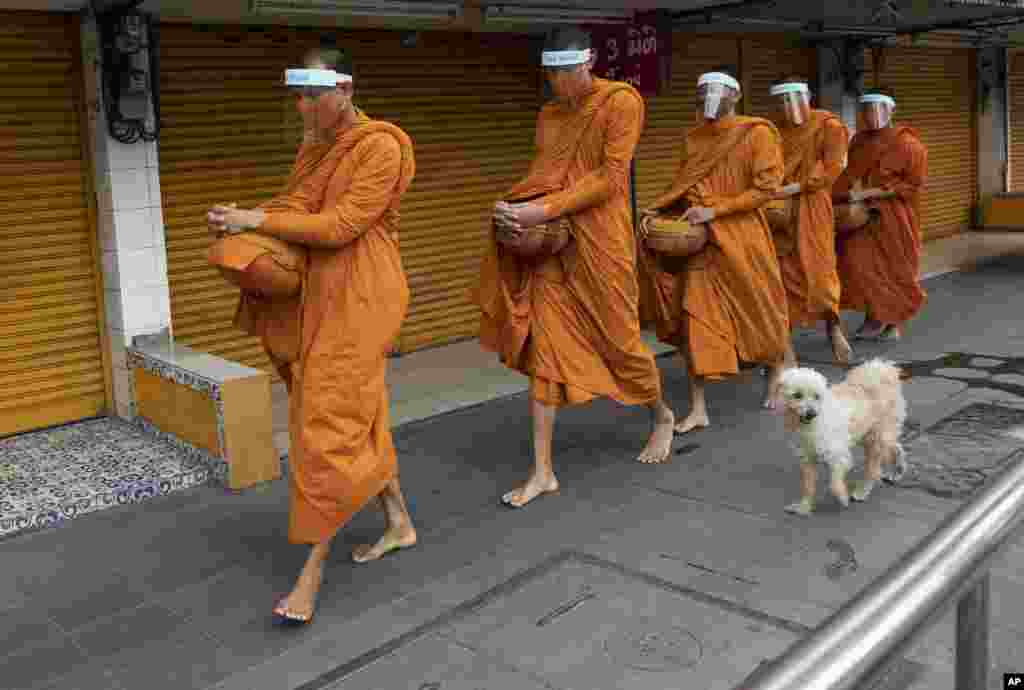 Buddhist monks with face covers to protect themselves from the new coronavirus walk to collect food donations in Bangkok, Thailand.