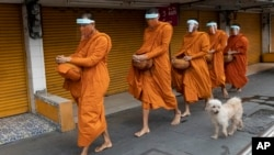 Thai Buddhist monks wear face shields to protect themselves from new coronavirus as they walk to collect alms from devotees in Bangkok, Thailand, Tuesday, March 31, 2020.