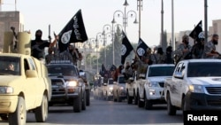 Islamic State fighters parade on military vehicles along the streets of Syria's northern Raqqa province.