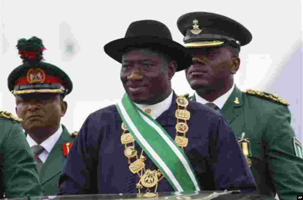 Nigerian President Goodluck Jonathan, center, inspects a guard of honor during his inauguration ceremony at the main parade ground in Nigeria's capital of Abuja, Sunday, May 29, 2011. Jonathan was sworn in Sunday for a full four-year term as president of