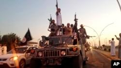 ພວກນັກລົບອິສລາມ ກຳລັງເດີນສວນສະໜາມທີ່ເມືອງ Mosul, ປະເທດອີຣັກ Iraq ວັນທີ 23 ທິຖຸນາ 2014.