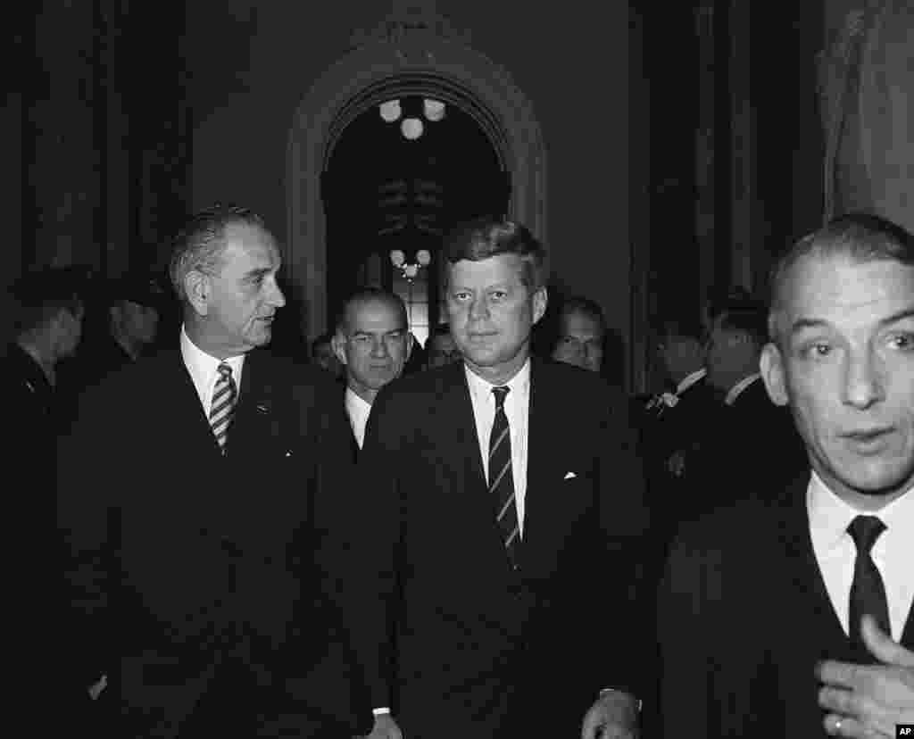 លោកប្រធានាធិបតី John F. Kennedy ដើរកាត់សាលរដ្ឋសភា ក្រោយពីបានថ្លែងសុន្ទរកថាស្តីពីស្ថានភាពប្រទេសជាតិ នៅមុខសមាជិករដ្ឋសភាដែលមានវត្តមាន កាលពីថ្ងៃទី៣០ ខែមករា ឆ្នាំ១៩៦១។ លោកប្រធានាធិបតី Kennedy ស្តាប់លោក Lyndon Johnson អនុប្រធានាធិបតី (ស្តាំ) មុននឹងបរិភោគអាហារថ្ងៃត្រង់។ (AP)